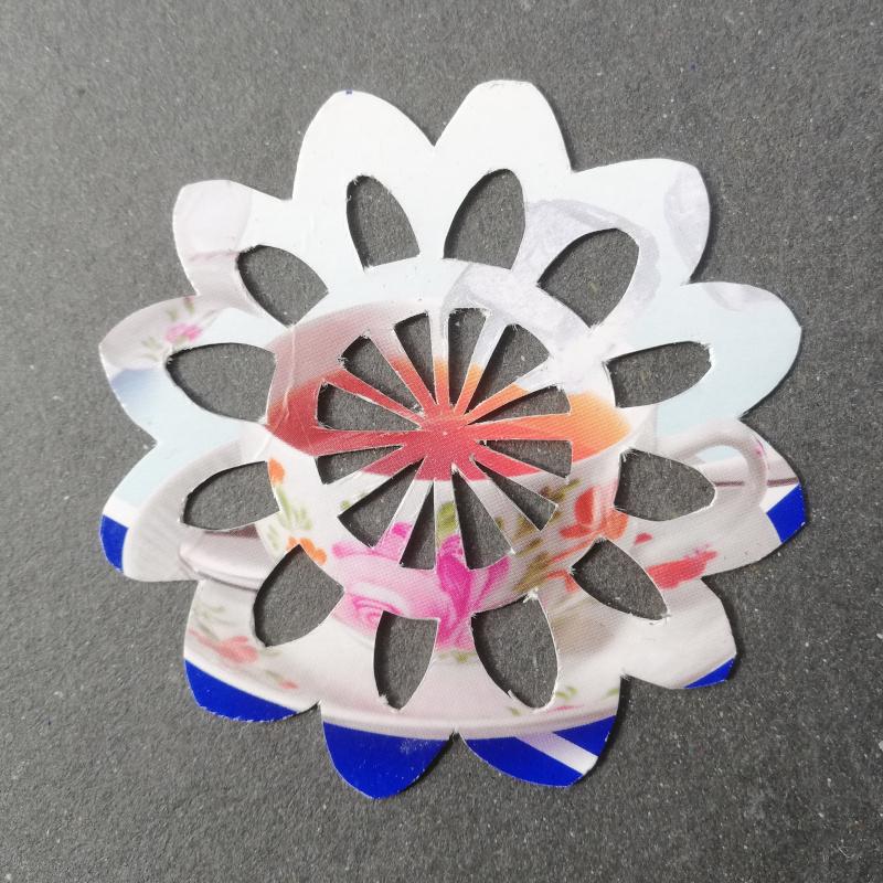 Ornament aus einer Kandiszuckerverpackung herausgeschnitten, ähnlich einer Häkeldecke